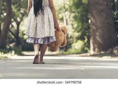 Sad girl feeling alone in the park. Lonely concepts. Beautiful toddler girl and fluffy stay alone under the big tree