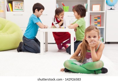 Sad girl feeling excluded from the group of playing kids
