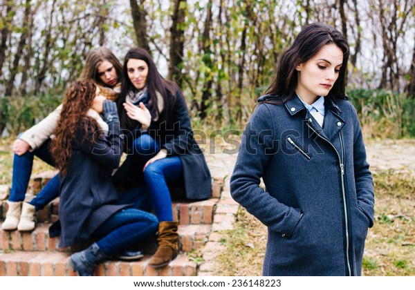 Sad girl with friends gossiping in background,  behind her back