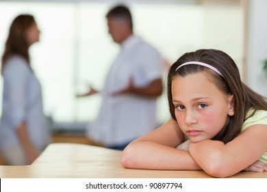 Sad girl with her fighting parents behind her