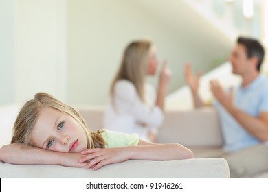Sad girl with her fighting parents in the background