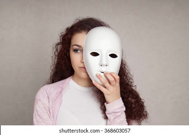 sad girl hiding behind mask