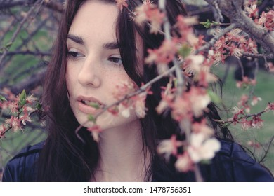 Sad girl hiding in cherry flower branches looking dawn