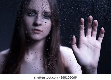 Sad girl holding hand on wet windshield