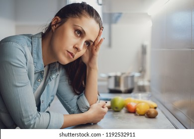 Sad girl leaning on the kitchen countertop and looking up while thinking