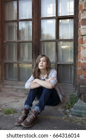 A sad girl with long hair in jeans of thirteen sits near big window