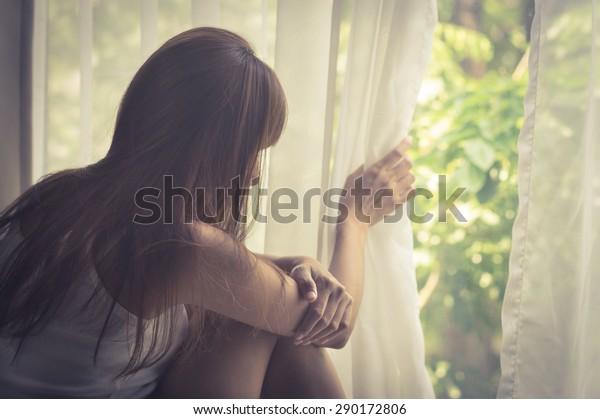 Ragazza triste che guarda fuori dalla finestra, vintage filtrato.