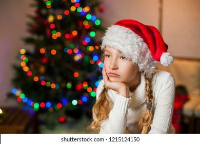 Sad girl near christmas tree looking away