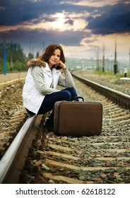 Sad girl on  railway sitting with her suitcase