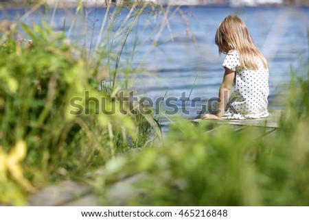 Sad girl on the riverbank