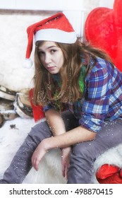 Sad girl in a plaid shirt and a cap of Santa Claus sitting on a chair. Santa Claus did not bring gifts.
