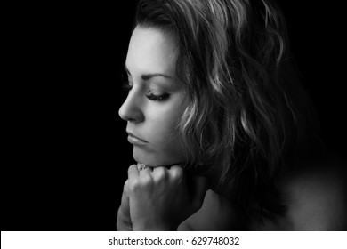 Sad girl profile, clasped hands, black and white