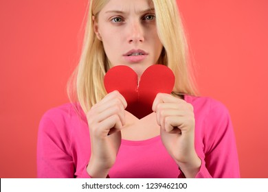 Sad girl with red broken paper heart. Negative sad emotions, relationship problems concept. Break of relations. Unrequited love. Angry girl tearing red heart. Pretty woman in pink dress breaking heart