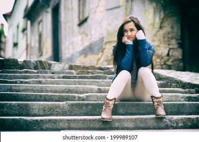 Sad girl sitting on a stairs