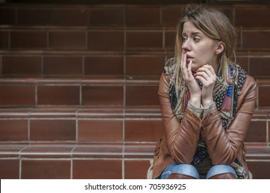 Sad girl sitting thoughtfully at the street. Girl in depression is standing sad on the stairs. Depressed teenager sitting lonely outdoors