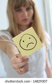 Sad girl with sad smile on note pad