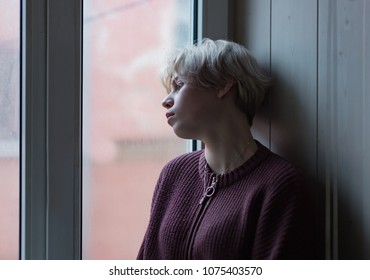 Sad girl standing by the window