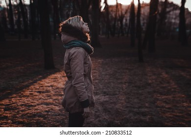 Sad girl standing in the park in autumn