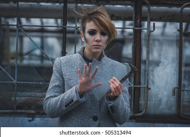 Sad girl standing with a piece of glass. She touches shard