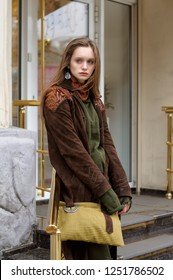 Sad girl stands near the shop window. She is dressed in a boho style: brown coat, yellow bag, green sweater, shorts and torn stockings