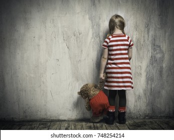 Sad girl with a toy bear standing back in the background of the textured walls. The concept of children's resentment, the complexity of education, the child's behavior