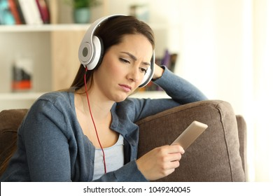 Sad girl wearing headphones listening to music sitting on a couch in the living room at home