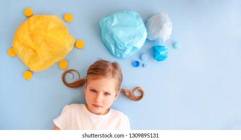 Sad girl and world of plastics. Plastic trash, plastic bags and garbage, straws. Plastic sun, sky, clouds. Environment pollution concept. Plastic free concept. Say no plastics.
