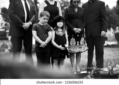 Sad grandkids standing by the grave