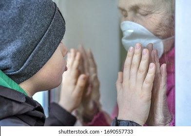 A sad grandmother mature woman in a respiratory mask communicates with grandchild through a window. Elderly quarantined, isolated. Pandemic coronavirus covid-19. Older people. Family values, care