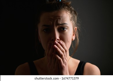 Sad grieve miserable desperate crying woman with tears eyes and folded hands on a dark black background during trouble, life difficulties, loss and emotional problems
