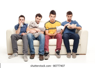 sad  group of young men looking at television sitting on a couch