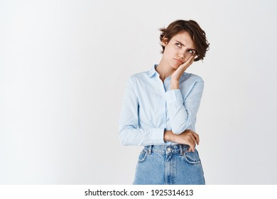 Sad and grumpy young woman in shirt, looking at upper left corner with offended angry face, frowning and standing jealous on white background.
