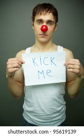 Sad guy with a �Kick me� note in hands on all fools day
