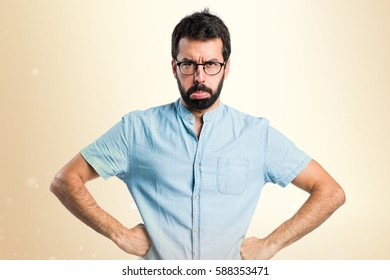 Sad handsome man with blue glasses on ocher background