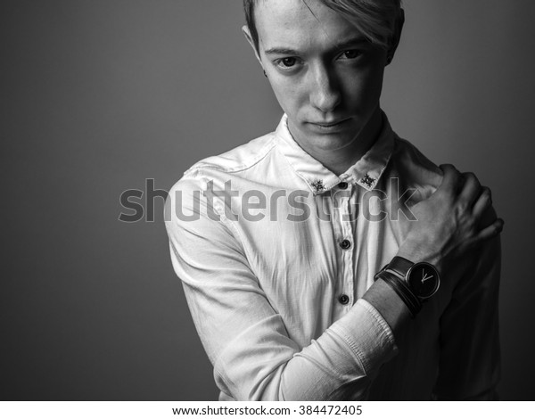 Sad handsome young man in a white shirt with blond hair. Black and white