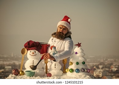 Sad hipster with ladle in white uniform. Man in santa hat ladling soup on winter day. Cook, snowmen and snow xmas tree on blue sky. Cooking and diet concept. Christmas and new year holidays food.