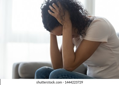 Sad hopeless young black woman sit alone at home feeling desperate depressed, upset stressed african girl suffer from alcohol abuse drug addiction, dependency, grief or guilt troubled with problems