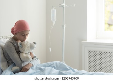 Sad ill teenager girl sitting alone in hospice bed, holding teddy bear, waiting for her doctor
