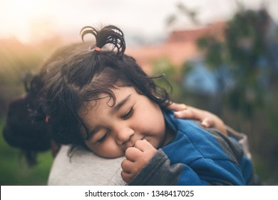 A Sad Indian Daughter Hugging Mother Outdoors. Mom with Her Kid, Little Girl with Frustrated Face Embracing Young Woman Outside.