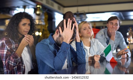 Sad Italian multiracial sport fans with flag disappointed about defeat in match
