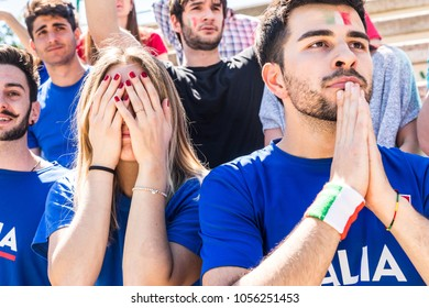 Sad Italian supporters at stadium after losing a match. Group of fans watching a match and being disappointed for the result. Sport and lifestyle concepts.
