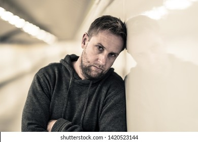 Sad jobless young man crying suffering depression stress sitting on ground street subway tunnel looking desperate leaning on wall alone in Mental disorder Emotional pain Drug abuse and Alcoholism.