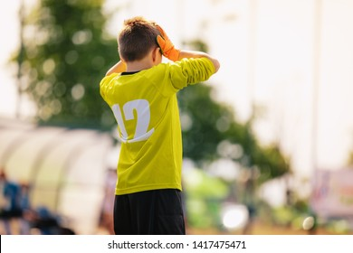 Sad junior soccer goalkeeper. Disappointed boy in yellow goalie sportswear kit with hands on his head. Junior youth football team loosing goal