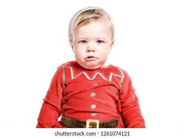 Sad kid dressed as Santa Claus. Christmas boy. One isolated on white background