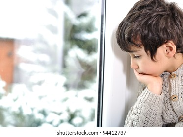 Sad kid on window cannot go out because of cold and snow