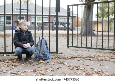 Sad kid at school fence waiting for his mother