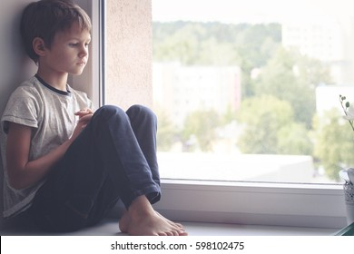 Sad kid sitting on window shield and looking out the window