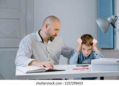 Sad kid sitting at a table with books and notebooks next to his father, who is angry at him.