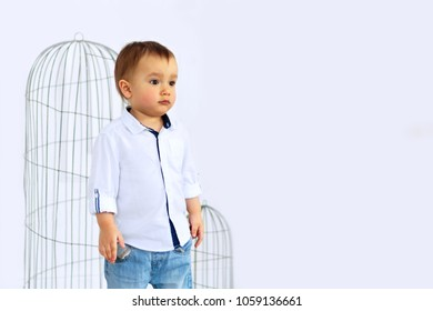 Sad kid in white shirt and jeans standing in front of empty bird cages. Bad parenting concept. Place for text.