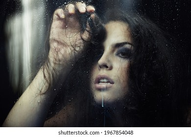 Sad lady in love behind the window wet after the rain